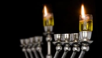 Traditional Chanukah menorah lit with olive oil, isolated on a black background; selective focus on the right flame.